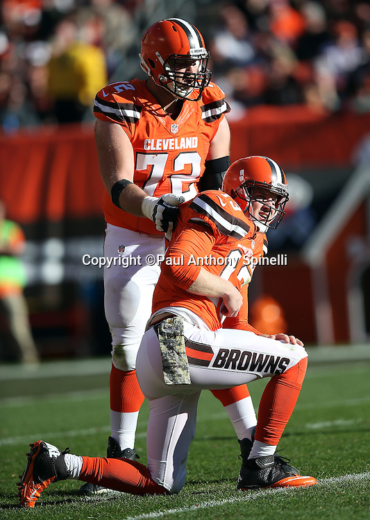 Cleveland Browns quarterback Josh McCown (13) gets help up off the ground from Cleveland Browns tackle Mitchell Schwartz (72) as he winces in pain after a hard hit during the 2015 week 8 regular season NFL football game against the Arizona Cardinals on Sunday, Nov. 1, 2015 in Cleveland. The Cardinals won the game 34-20. (©Paul Anthony Spinelli)