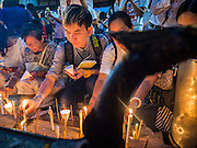 24 AUGUST 2015 - BANGKOK, THAILAND:  People light candles for the victims of the Erawan Shrine bombing. One week after the a bomb at the Erawan Shrine in the center of Bangkok killed dozens and hospitalized scores of people, police have not made any arrests. Police bomb sniffing dogs have been deployed to malls and markets around Bangkok. There was a large memorial service sponsored by businesses close the bomb site Monday evening.      PHOTO BY JACK KURTZ