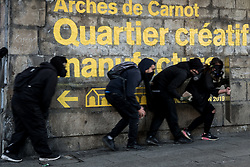 March 30, 2019 - Saint Etienne, France - Protestors in black sneak around a corner during Regional rally on the occasion of the twentieth day of mobilisation of the Yellow Vests in Saint Etienne, France. (Credit Image: © Nicolas Liponne/NurPhoto via ZUMA Press)