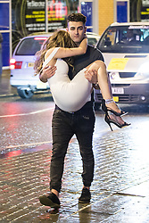 © Licensed to London News Pictures . 01/01/2015 . Manchester , UK . A man carries a woman . Revellers usher in the New Year on a night out in Manchester City Centre .  Photo credit : Joel Goodman/LNP