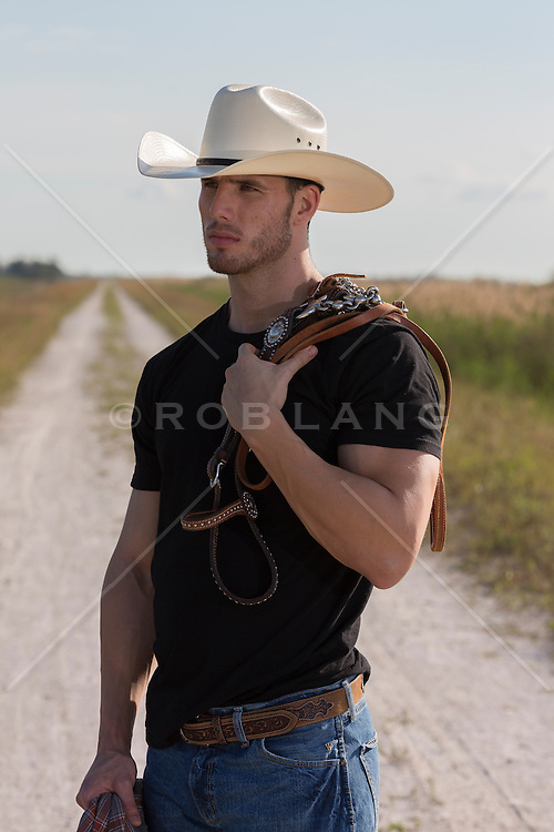 rugged cowboy in a black tee shirt standing on a dirt road