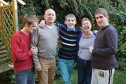 Family portrait of parents with three sons with autism. Cleared for Mental Health issues.