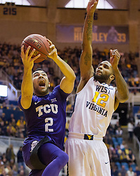 Jan 7, 2017; Morgantown, WV, USA; TCU Horned Frogs guard Michael Williams (2) shoots in the lane guarded by West Virginia Mountaineers guard Tarik Phillip (12) during the first half at WVU Coliseum. Mandatory Credit: Ben Queen-USA TODAY Sports