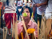 01 JANUARY 2016 - BANGKOK, THAILAND:          A woman prays with incense sticks and a lotus bud during the annual New Year's mass merit making ceremony on at Sanam Luang in Bangkok. The ceremony is sponsored by the Bangkok city government. More than 500 Buddhist monks participated in the ceremony this year. Thais usually go to temples and religious observances to meditate and make merit on New Year's Day.     PHOTO BY JACK KURTZ