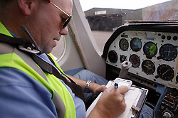Man with disability; who is wheelchair user; sitting in aircraft cockpit preparing to fly plane,