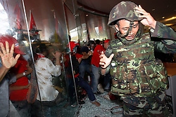 A Thai army officer is cut by broken glass when red shirt protesters broke the glass walls of the Pattaya Exhibition and Convention Centre, the venue for the Association of South East Asian Nations (ASEAN)-China plus six summit in Pattaya, Thailand, 11 April 2009. Thai government decided to postpone indefinitely the Asean summit after thousands of red-shirts protesters loyal to fugitive former premier Thaksin Shinawatra broke into a hotel where is the venue of the summit of the Association of South-East Asian Nations (ASEAN) at the Thai seaside resort of Pattaya.