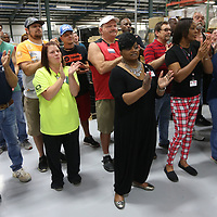 Pride Mobility employees applaud during the unvieling of the new Victory scooter on Thursday.