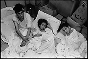 Beirut, Lebanon August 4th 1982. Basement of the Barbir hospital in W.Beirut near by the Green line.Patients of the hospital have been moved from their rooms to the basement, while Israeli bombings are raging outside. The woman  and her two children were injured by the explosion of phosphorous rockets. ©Herve Merliac