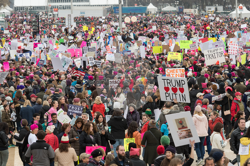 Demonstrators wave signs during the Women's March on Washington in protest to President Donald Trump January 21, 2017 in Washington, DC. More than 500,000 people crammed the National Mall in a peaceful and festival rally in a rebuke of the new president.