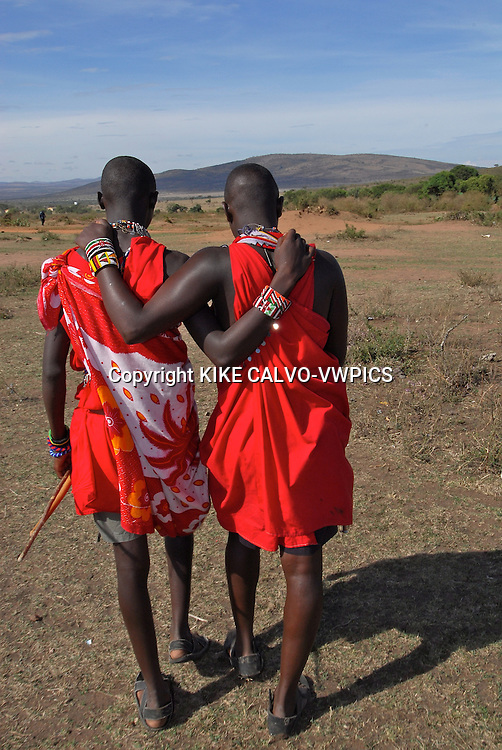 Two brothers show their bond while walking arm over arm. Masai Mara tribe around the Masai Mara National Park. Kenya. East Africa.