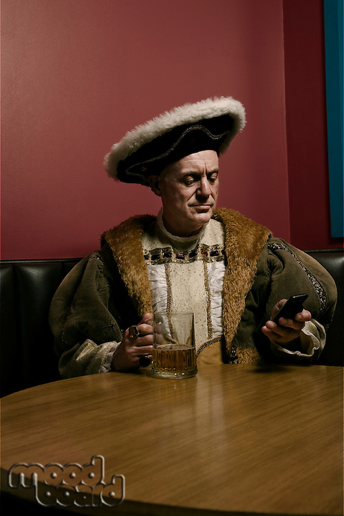 King Henry VIII using mobile phone at table