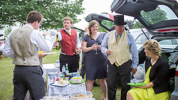 © Licensed to London News Pictures. 19/06/2014. Ascot, UK. The Kevis family and friends picnic amongst cars in the car park.  Day three, Ladies Day, at Royal Ascot 19th June 2014. Royal Ascot has established itself as a national institution and the centrepiece of the British social calendar as well as being a stage for the best racehorses in the world. Photo credit : Stephen Simpson/LNP