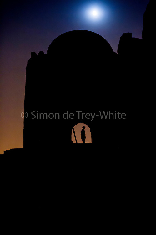 4th December 2014, New Delhi, India. Moonrise over the ruins of Feroz Shah Kotla as people come to make offerings to Djinns in the hopes of getting wishes granted, New Delhi, India on the 4th December 2014<br /> <br /> PHOTOGRAPH BY AND COPYRIGHT OF SIMON DE TREY-WHITE a photographer in delhi<br /> + 91 98103 99809. Email: simon@simondetreywhite.com<br /> <br /> People have been coming to Firoz Shah Kotla to leave written notes and offerings for Djinns in the hopes of getting wishes granted since the late 1970's. Jinn, jann or djinn are supernatural creatures in Islamic mythology as well as pre-Islamic Arabian mythology. They are mentioned frequently in the Quran  and other Islamic texts and inhabit an unseen world called Djinnestan. In Islamic theology jinn are said to be creatures with free will, made from smokeless fire by Allah as humans were made of clay, among other things. According to the Quran, jinn have free will, and Iblis abused this freedom in front of Allah by refusing to bow to Adam when Allah ordered angels and jinn to do so. For disobeying Allah, Iblis was expelled from Paradise and called &quot;Shaytan&quot; (Satan).They are usually invisible to humans, but humans do appear clearly to jinn, as they can possess them. Like humans, jinn will also be judged on the Day of Judgment and will be sent to Paradise or Hell according to their deeds. Feroz Shah Tughlaq (r. 1351&ndash;88), the Sultan of Delhi, established the fortified city of Ferozabad in 1354, as the new capital of the Delhi Sultanate, and included in it the site of the present Feroz Shah Kotla. Kotla literally means fortress or citadel.