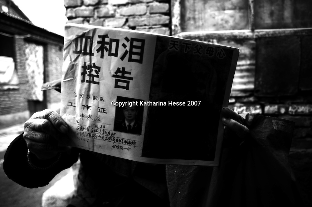 "BEIJING, DECEMBER-26:  a woman holds a leaflet titled "" Blood and tears "" that relates a family members unfair treatment .. In the past decades, hundreds of thousands of Chinese from the provinces have descended upon Beijing in hopes of attracting attention from higher authorities regarding their civil law cases. These cases vary from work accidents, violence against family members, murder, extortion, and the majority of which stem from a corrupt rural legal system...The tradition of petitioning to higher authorities in the Chinese capital reaches back to Imperial times. Outside the city center of Beijing, petitioners' villages sprung up as those seeking justice face long delays in being heard. The petitioners today face tremendous obstacles in having their cases heard; authorities are overworked due to the sheer number of complaints, which are often clumsily presented without aid of a legal adviser. In addition, Provincial as well as undercover police try to stop the petitioners from going to the National Petition offices to file their cases. If caught, they are briefly sent to an unofficial detention centre where they are held and forced to take the train back to the provinces. For many of the petitioners, it has become their life mission to make the regular journey to the capital only to be sent back without ever having been heard...The number of petitioner villages has been reduced significantly as the preparations for the 2008 Olympics progress. Many fear these villages will be gone by the summer of 2008.."