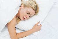 Young woman in pain lying on bed