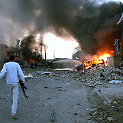 28 Jan 2004.Baghdad, Iraq..Bomb Attack on Baghdad Hotel..A suspected suicide bomber attacked the Shaheen Hotel in the early hours. .A team of South African security guards working for 'Erinys Iraq were amoung the casualties, at least two of their number were killed as a result of the explosion..A barefoot Iraqi gunman strides towards the hotel minutes after the blast...
