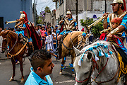 Actors playing Roman calvary sound their trumpets as the processions winds its way through central Iztpalapa.