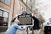 """MONTGOMERY, AL – DECEMBER 9, 2013: <br /> One of three new markers describing the city of Montgomery's involvement in the slave trade is carried for installation on Commerce Street in downtown Montgomery. Bryan Stevenson, the Executive Director of Equal Justice Initiative, states that the new markers are a culmination to a sustained effort to """"create a more concrete visual relationship with the history of the region."""" CREDIT: Bob Miller for The New York Times"""