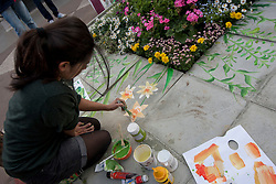© licensed to London News Pictures. London, UK 21/04/2012. A girl painting flowers next to the real flowers in Trafalgar Square as the London landmark transformed into an English garden ahead of St George's Day. Photo credit: Tolga Akmen/LNP