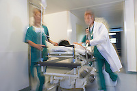 Doctors running Patient on gurney through hospital corridor motion blur