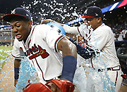 ATLANTA, GA - AUGUST 14:  Left fielder Ronald Acuna, Jr. #13 of the Atlanta Braves gets a Powerade bath from teammates Charlie Culberson #16 (behind) and Johan Camargo #17 (right) after the game against the Miami Marlins at SunTrust Park on August 14, 2018 in Atlanta, Georgia.  (Photo by Mike Zarrilli/Getty Images)
