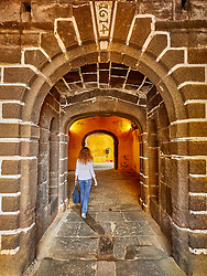 Redhead lady walks through arches at  Saint Tiago Fortress, Funchal, Madeira.