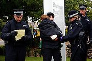 Climate change activists are being frisked by the UK police during a 24 hours mass action in front of the British Airport Association (BAA), close to Heathrow airport to protest against climate change and the expansion plans for the airport on Sunday, Aug. 19, 2007, Heathrow, England. More than 1800 police officers were deployed to counter the activists in their plan to disrupt the BAA activities on the site. Aviation is the fastest growing source of greenhouse gas emissions in the UK, and all our efforts to tackle climate change in other sectors are undone by the massive growth in air travel. Holding the camp at Heathrow aims to highlight the paradoxical government's airport expansion plans, target industry giants profiteering from the climate crisis, and raise awareness about the need to fly less. The camp also support local residents in their long-term struggle against the building of a third runway and the destruction of their communities. Heathrow, the world's busiest international airport, has been the target of Climat Camp campaing in 2007. www.climatecamp.org.uk   **Italy Out** .