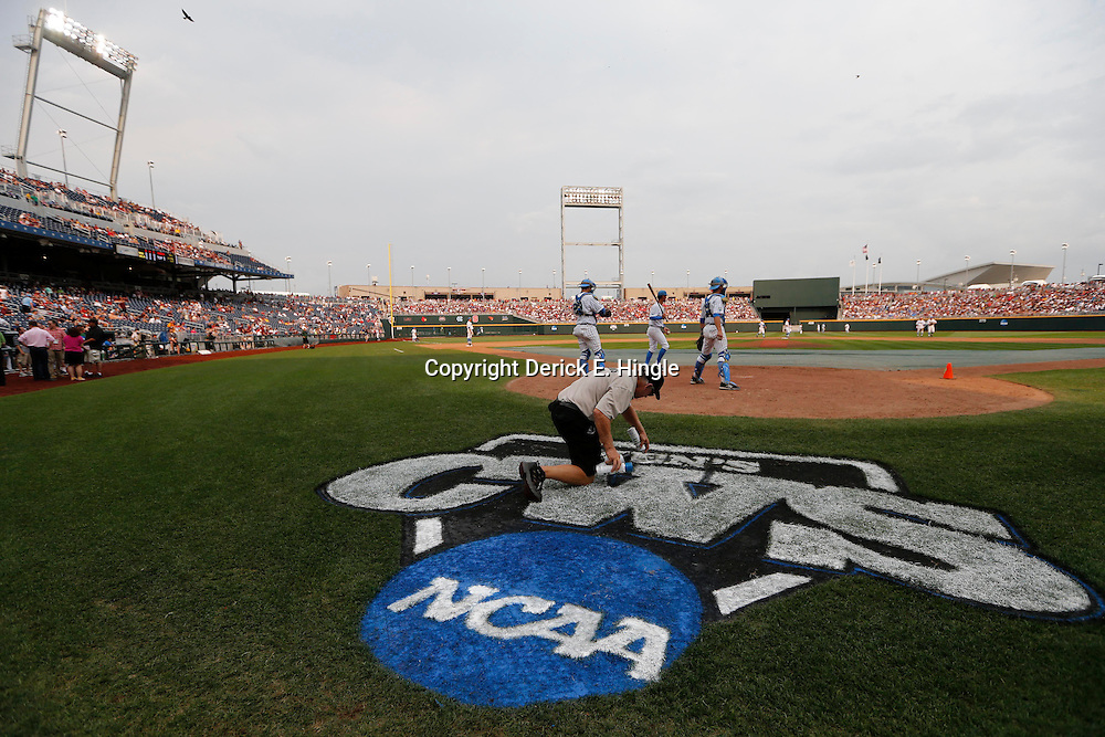 Jun 25, 2013; Omaha, NE, USA; A grounds crew member paints the logo before game 2 of the College World Series finals at TD Ameritrade Park between the UCLA Bruins and the Mississippi State Bulldogs. Mandatory Credit: Derick E. Hingle-USA TODAY Sports