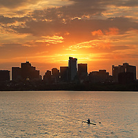 Early morning sunrise skyline photography image of Beacon Hill and the Massachusetts State House with newly constructed Millennium Tower in Boston. A single scull with one rower working out hard and pushing through a morning fitness workout rowing upstream in the orange reflection of the morning sky on the Charles River.<br />