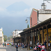 With some of the buildings ringing Parque Central in Antigua, Guatemala, in the foreground, the Volcán de Agua can be seen partially obscured in the background.