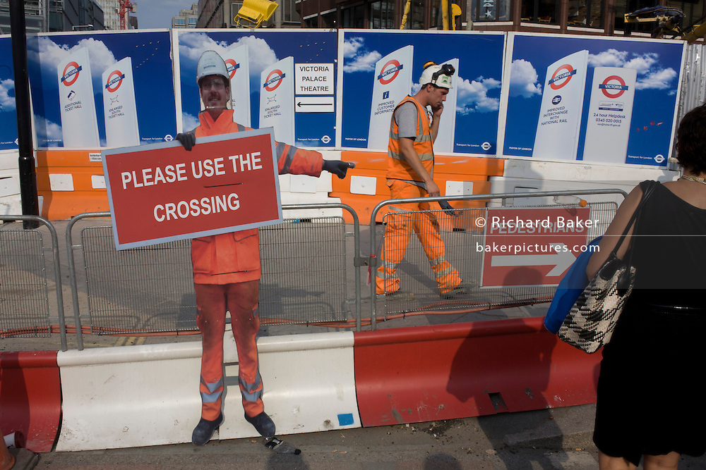 Construction worker and cut-out site character telling pedestrians crossing a London Victoria street development.