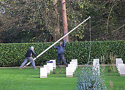 © Licensed to London News Pictures. 23/11/2015. London, UK. Commonwealth War Graves Commission staff bring down a vandalised flag pole at the Australian Military Cemetery next to St Mary's Parish Church in Harefield. Vandals had attempted to saw through the flagpole. Photo credit: Peter Macdiarmid/LNP