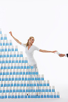 Man (close-up of hand) handing woman plastic cup for stacked pyramid against white background