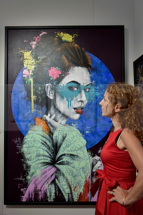 """© Licensed to London News Pictures. 06/10/2017. London, UK.  A woman views """"Yuansu"""" by Fin Dac at the Moniker Art Fair, the world's biggest urban art fair, taking place at the Old Truman Brewery in East London from 5 to 8 October 2017.  The fair brings together the world's most influential new-contemporary and urban art galleries to show international artworks to Londoners. Photo credit : Stephen Chung/LNP"""