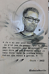 """© Licensed to London News Pictures. 07/01/2016. Paris, France. Grafitti showing the image of 5 cartoonists of the satirical magazine Charlie Hebdo killed during on january 7th 2015 by 2 terrorists which sparked a manhunt that lasted 3 days. A text and image of """"Charb"""" Stephane Charbonnier is on the other side of the wall. Today January 3rd 2016. Photo credit: Hugo Michiels/LNP"""