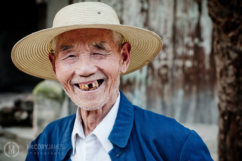 An elderly Chinese man laughs on the street in Hanzhong, China.