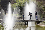 © Licensed to London News Pictures. 07/04/2015. Maidenhead, UK. People cross a bridge into the water garden. People enjoy the warm and sunny weather at Cliveden House in Maidenhead Buckinghamshire today 7th April 2015. Photo credit : Stephen Simpson/LNP