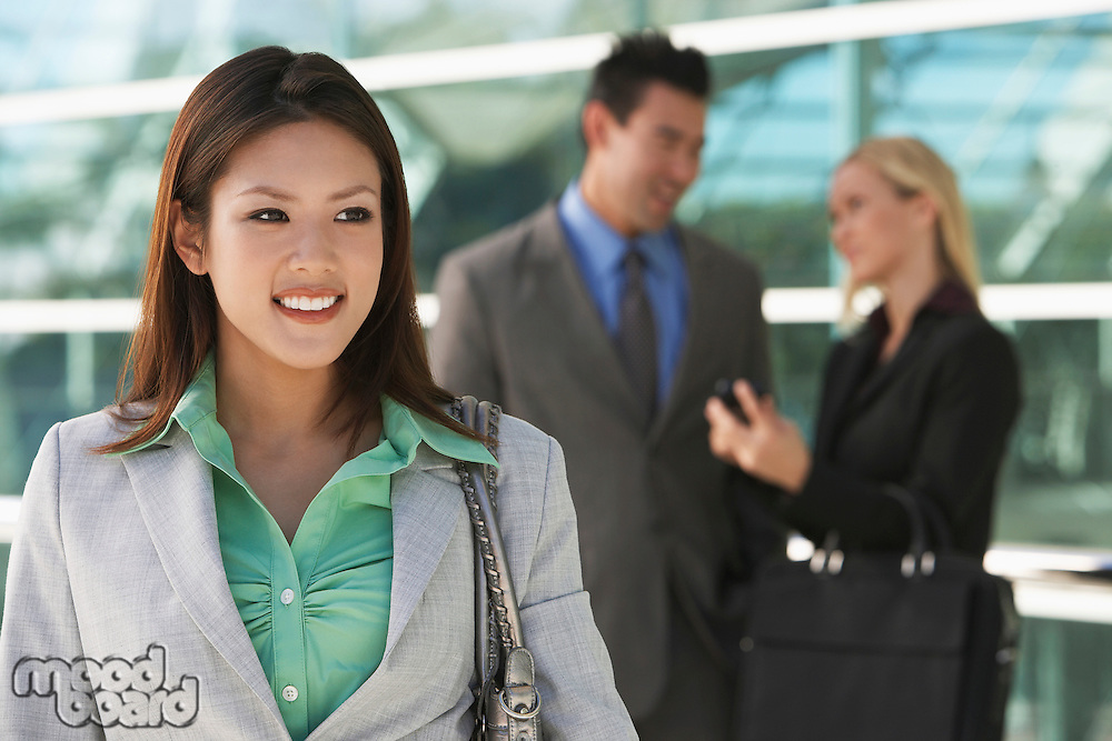 Businesswoman smiling with colleagues in background, outdoors