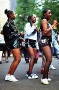 Three girls dancing in the road, Notting Hill Carnival, London UK 2000's