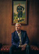 Hillerich & Bradsby CEO John Hillerich poses for a portrait under a painting of Louisville Eclipse player Pete Browning, the first professional baseball player to use a Louisville Slugger, at the Louisville Slugger Museum.