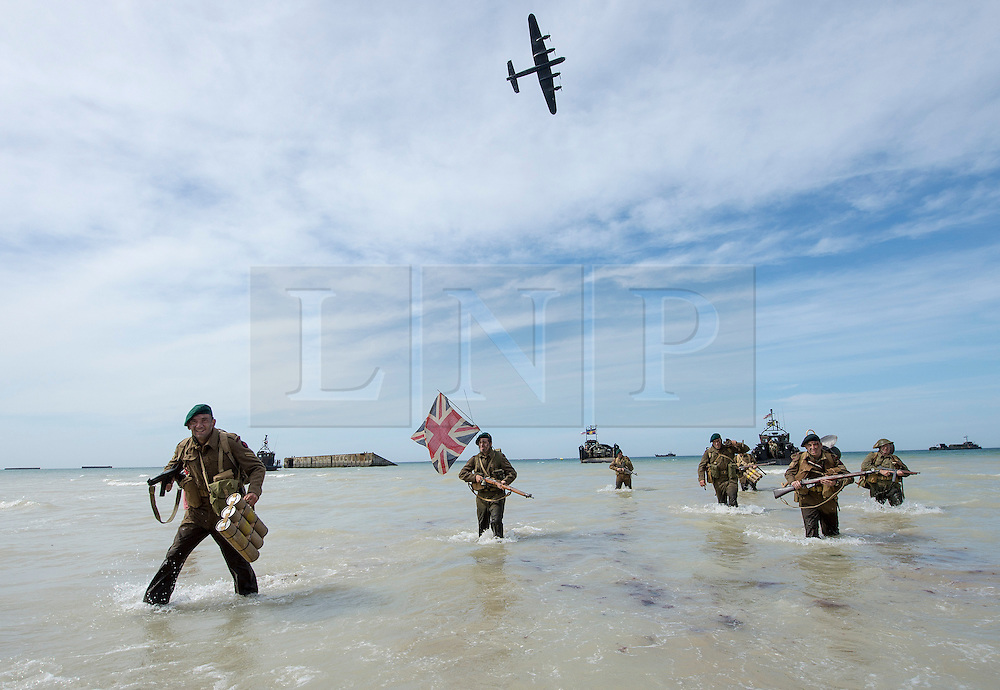 © Licensed to London News Pictures. 06/06/14. Arromanches,. Pictured: Members of a Spanish re-enactment group, dressed as Royal Marine Commandos, 'storm' up Gold beach in Arramanches after disembarking from a Royal Navy landing craft., much to the delight of the gather crowds. They boarded Battle of Britain Memorial Flight flew over. The enthusiasts were all dressed as Royal Marine Commandoes.<br />  Photo credit : Cpl Jamie Peters RLC/LNP