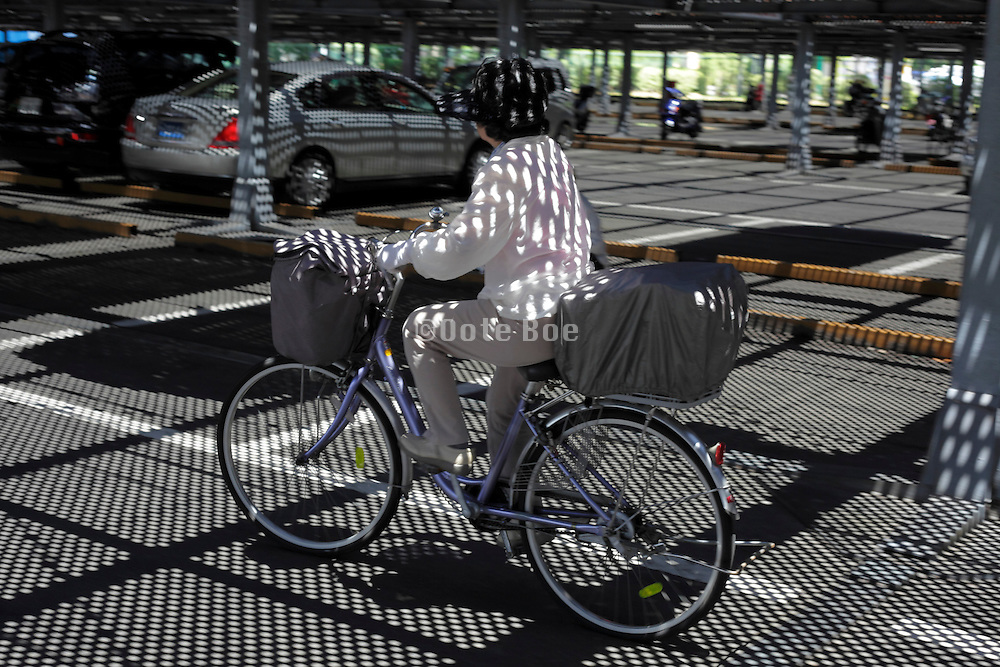 bicycling person with strong sun shadow projection of overhead grill