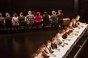 Brooklyn, NY - 11 December 2019. A performance of In Many Hands in BAM's Fishman Space, by Kate McIntosh in collaboration with Arantxa Martinez and Josh Rutter; sound design by John Avery; lighting design by Joëlle Reyms. The piece involves participants sitting at 3 long, narrow tables, with facilitators at each end, and either passing along objects—here rocks of varying shapes and sizes—or repeating hand movements in the manner set by a facilitator.
