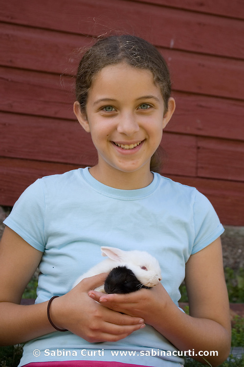 Family farm, young girl holds baby bunny rabbits on small sustainable family farm in Hillsdale, Columbia County, NY, New York.