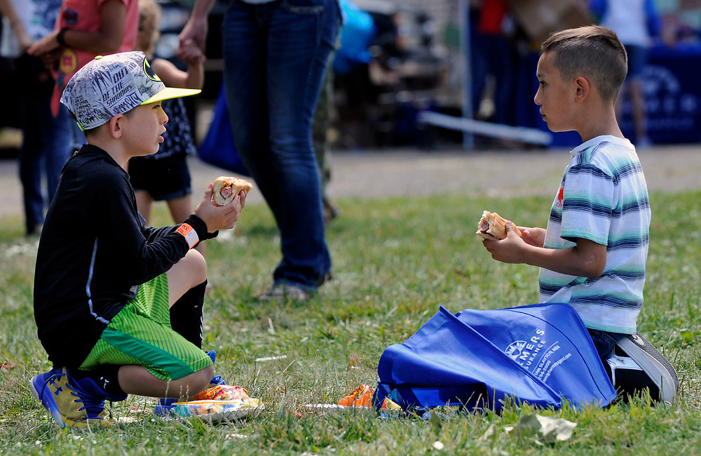 jt071417b/ a sec/jim thompson/left to right- Antonio Lay Barrios-8 and Xavier Dominguez enjoy their lunch of hot dogs at Rotary Park in Bernalillo,NM  as they attend the Cops in the Park celebration. Friday,  July. 14, 2017. (Jim Thompson/Albuquerque Journal)