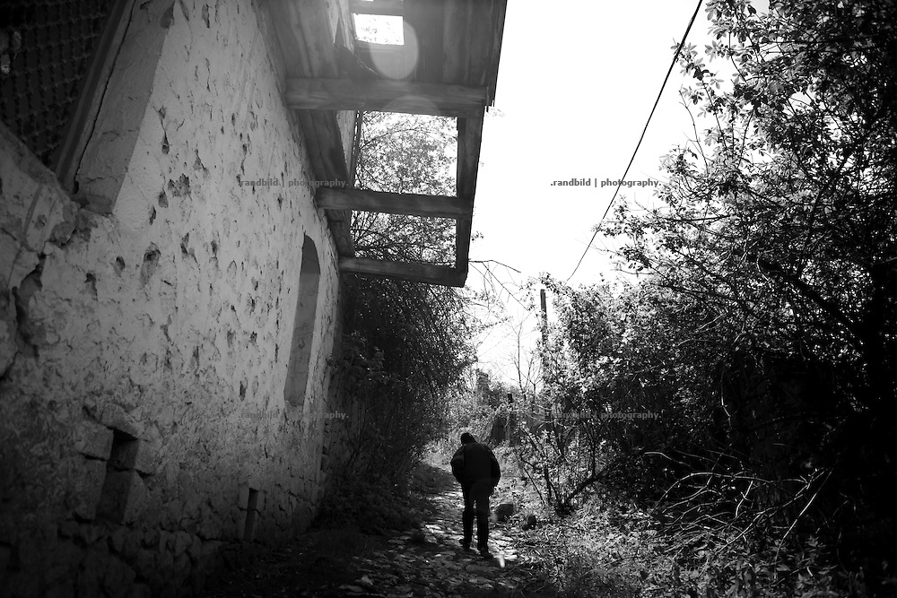 "A boy pass a war damaged house beside a little path in Shushi. This image is part of the photoproject ""The Twentieth Spring"", a portrait of caucasian town Shushi 20 years after its so called ""Liberation"" by armenian fighters. In its more than two centuries old history Shushi was ruled by different powers like armeniens, persians, russian or aseris. In 1991 a fierce battle for Karabakhs independence from Azerbaijan began. During the breakdown of Sowjet Union armenians didn´t want to stay within the Republic of Azerbaijan anymore. 1992 armenians manage to takeover ""ancient armenian Shushi"" and pushed out remained aseris forces which had operate a rocket base there. Since then Shushi became an ""armenian town"" again. Today, 20 yeras after statement of Karabakhs independence Shushi tries to find it´s opportunities for it´s future. The less populated town is still affected by devastation and ruins by it´s violent history. Life is mostly a daily struggle for the inhabitants to get expenses covered, caused by a lack of jobs and almost no perspective for a sustainable economic development. Shushi depends on donations by diaspora armenians. On the other hand those donations have made it possible to rebuild a cultural centre, recover new asphalt roads and other infrastructure. 20 years after Shushis fall into armenian hands Babies get born and people won´t never be under aseris rule again. The bloody early 1990´s civil war has moved into the trenches of the frontline 20 kilometer away from Shushi where it stuck since 1994. The karabakh conflict is still not solved and could turn to an open war every day. Nonetheless life goes on on the south caucasian rocky tip above mountainious region of Karabakh where Shushi enthrones ever since centuries."