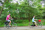 In Soest rijdt een man met zijn zoon op de fiets in de bossen.<br />