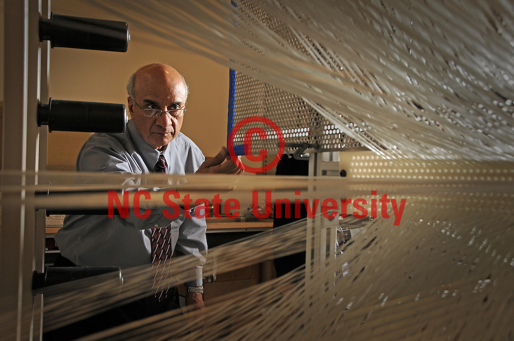 Abdel-Fattah Seyam looks over fibers in the 3D weaving machine at the College of Textiles.