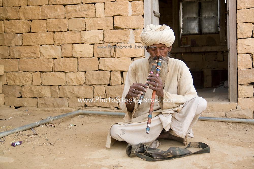 India, Rajasthan, Kuldhara village ruins near Jaisalmer. Snake charmer