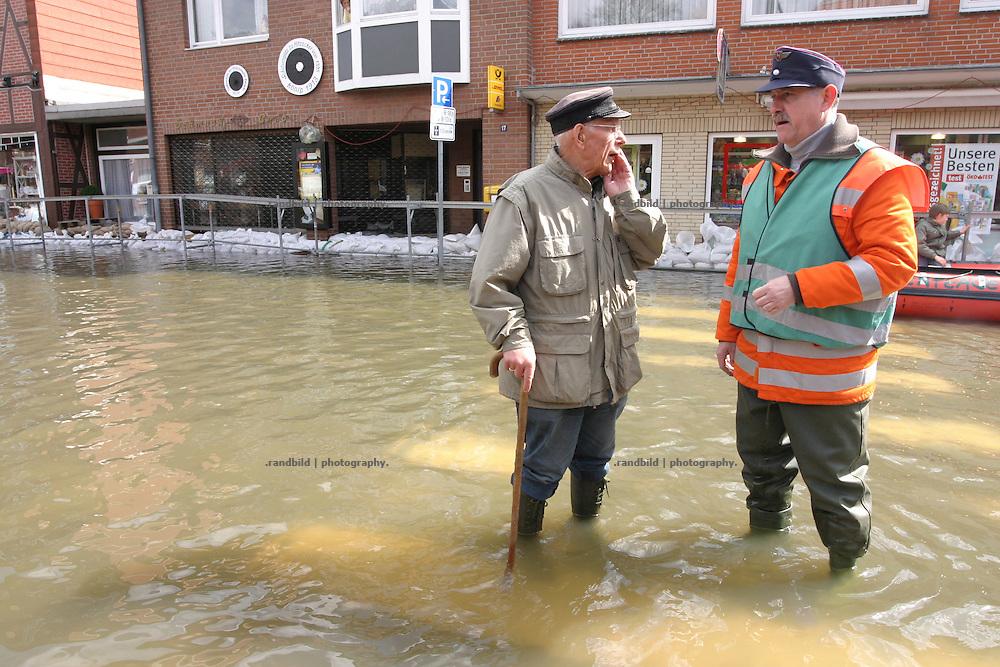 Ein Rentner aus Hitzacker steht mit einem Feuerwehrmann für eine Unterhaltung im Wasser der überfluteten Stadt. An old man talks to a fire fighter in the floods of Hitzacker.